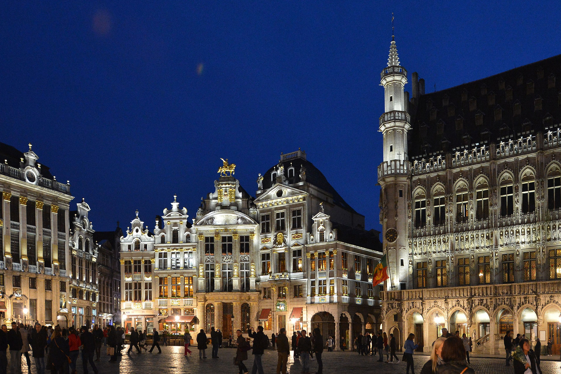 White light bathes the façades of Grand Place, highlighting their intricate architectural details