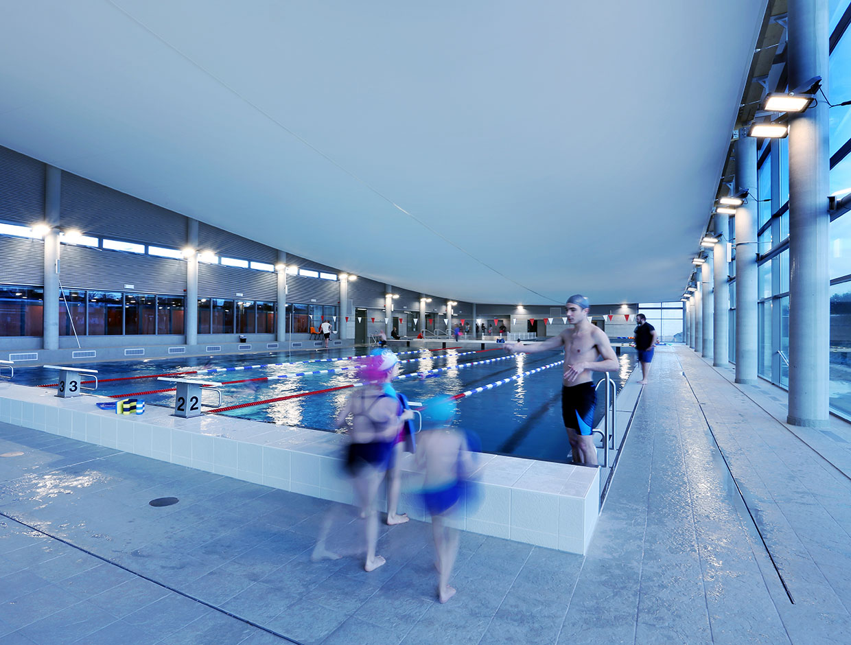 Intelligent lighting solution adapts levels to natural levels outside, reducing energy costs for this swimming pool